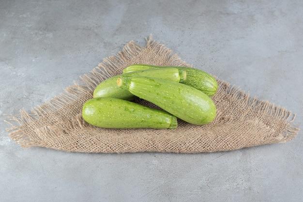 Vier frisches zucchini-gemüse auf einem sackleinen. foto in hoher qualität