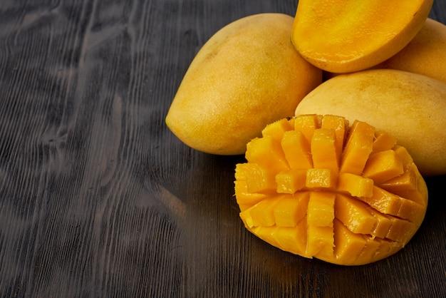 Vier ganze mangofrüchte auf holztisch und in scheiben schneiden.