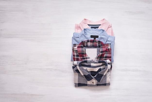 Vier gefaltete hemden auf hölzernem hintergrund. platz für text. modekonzept