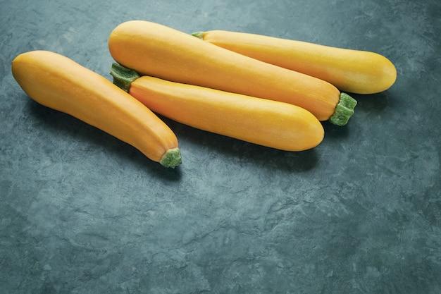 Vier gelbe zucchini auf küchentisch