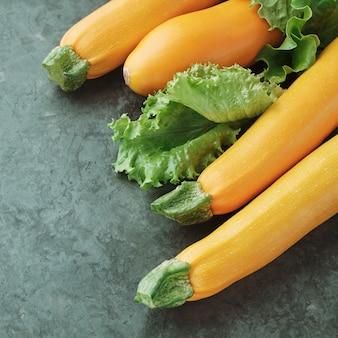Vier gelbe zucchini und salat auf küchentisch