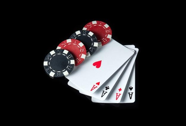 Vier gleiche oder viererkarten und chips im schwarzen hintergrund. gewinnkombination in einem pokerclub oder casino