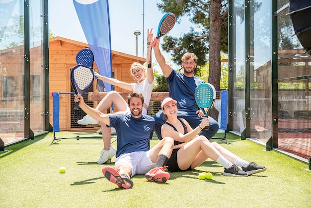 Vier glückliche gewinnende padel-tennisspieler feiern nach dem sieg des spiels