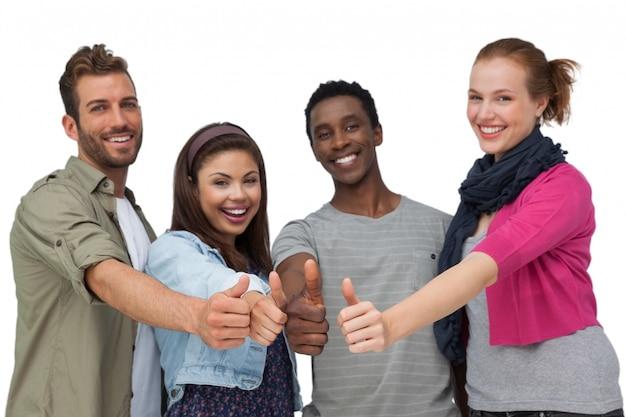 Vier glückliche junge freunde, die oben daumen gestikulieren