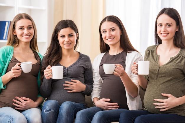 Vier glückliche schwangere frauen mit einer tasse tee.
