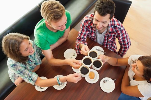 Vier glückliche studenten, die einen tasse kaffee unterhalten
