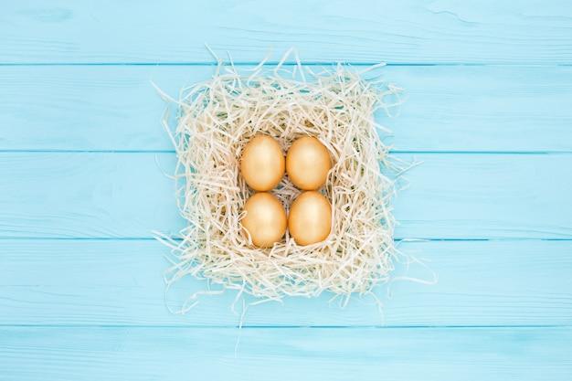 Vier goldene ostereier im quadratischen nest auf blauem hintergrund, flach gelegt.