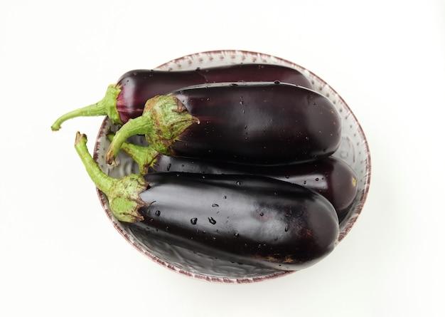 Vier große auberginen mit wassertropfen auf einem teller