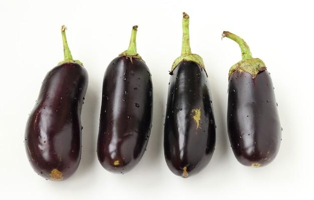 Vier große auberginen mit wassertropfen, weißer hintergrund, bio-lebensmittelkonzept, nahaufnahme, draufsicht