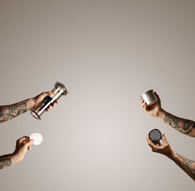 Vier hände mit aeropresse, filtern, filterkappe und stahlreisetasse reichen von der seite in die mitte des weißen werbespots für alternative kaffeezubereitung