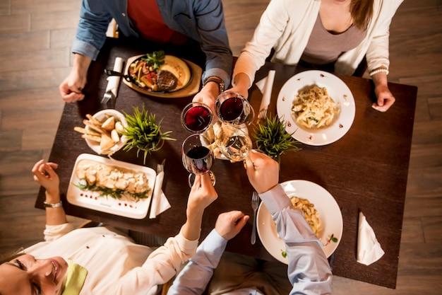 Vier hände mit rotwein, der über dem servierten tisch mit essen röstet