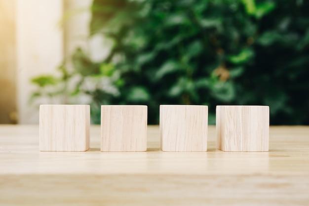 Vier hölzerne spielzeugwürfel auf hölzernem tischhintergrund mit kopienraum