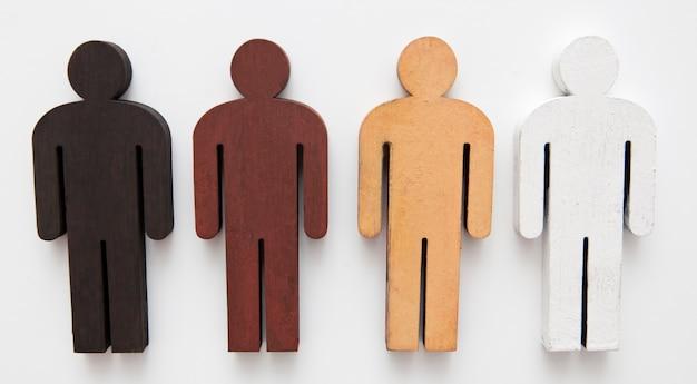 Vier holzfiguren mit unterschiedlicher farbe auf dem tisch