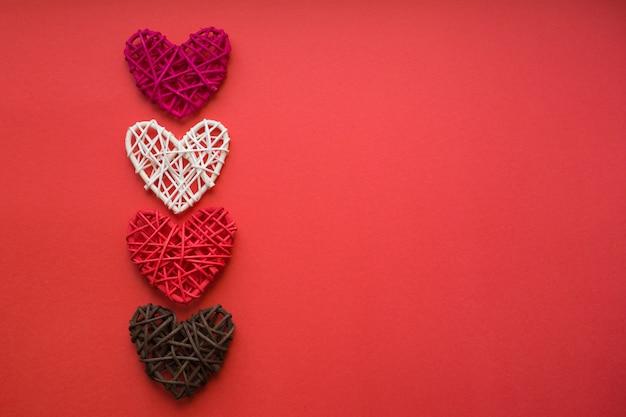 Vier holzherzen liegen aufrecht auf einem roten hintergrund. liebeskonzept. valentinstagskarte. platz für text