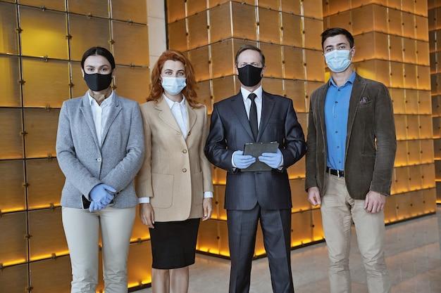Vier hotelangestellte stehen in der halle und tragen während der pandemie masken und gummihandschuhe