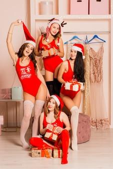 Vier hübsche junge frauen mit lockigem haar und roten weihnachtswäsche