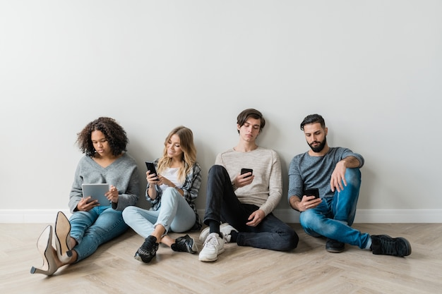 Vier interkulturelle millennials in freizeitkleidung sitzen an der weißen wand, während sie in ihren smartphones scrollen oder sms schreiben