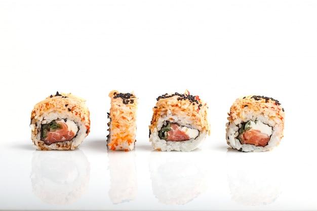 Vier japanische maki-sushi-rollen in einer reihe mit lachs, sesam und frischkäse lokalisiert auf weißem hintergrund. seitenansicht