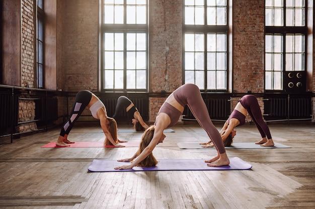 Vier junge frauen dehnen yoga-asanas im loft-stil. adho mukha svanasana - abwärts gerichtete hundepose.
