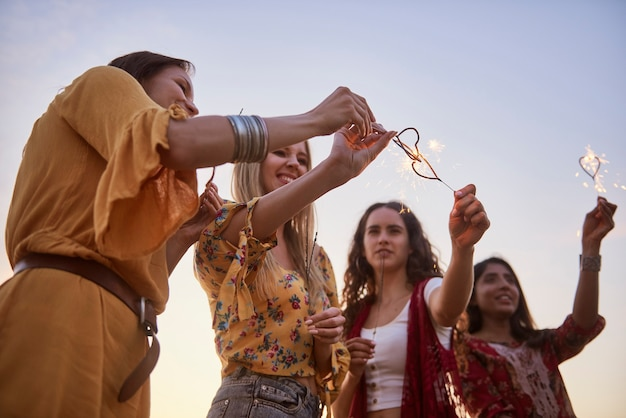 Vier junge frauen mit brennenden wunderkerzen bei sonnenuntergang