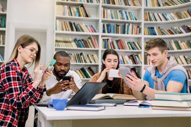Vier junge freunde, studenten, jungen und mädchen gemischter abstammung, die sich auf prüfungen vorbereiten und die benötigten informationen auf ihren smartphones suchen