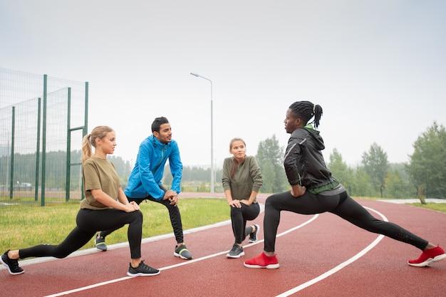 Vier junge freundliche aktive menschen in sportbekleidung, die auf rennstrecken im stadion in natürlicher umgebung trainieren
