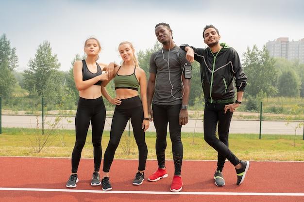 Vier junge freundliche interkulturelle menschen in sportbekleidung, die auf der rennstrecke des freiluftstadions in der städtischen umgebung stehen