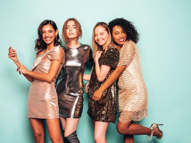 Vier junge internationale schöne brunettefrauen im modischen glänzenden sommerkleid.