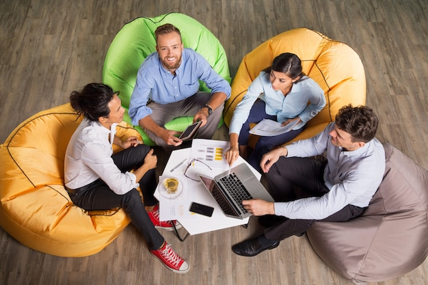 Vier junge kollegen auf beanbag stühle arbeiten