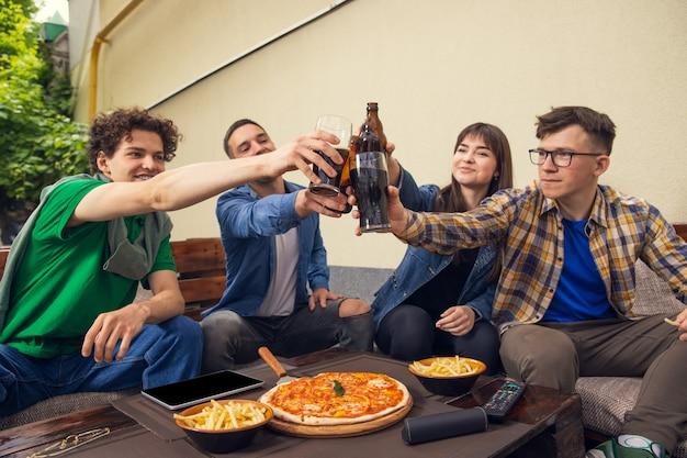 Vier junge leute, sportliche fans treffen sich in der bar. konzept der freundschaft, freizeitbeschäftigung