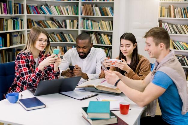 Vier junge leute, zwei jungen und zwei mädchen, sitzen am tisch, arbeiten zusammen, benutzen ihre smartphones, ihren laptop und ihre bücher