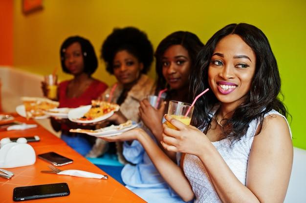 Vier junge mädchen im bunten restaurant mit pizzastücken auf teller und säften
