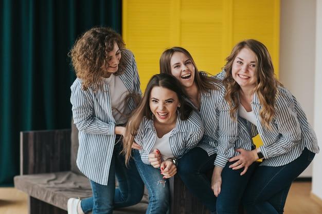 Vier junge mädchen in gestreiften hemden, jeans und turnschuhen posieren auf der couch