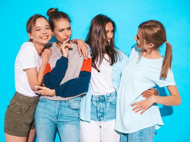 Vier junge schöne lächelnde hippie-mädchen in der modischen sommerkleidung. sexy sorglose frauen, die nahe blauer wand im studio aufwerfen. positive models, die spaß haben und umarmen
