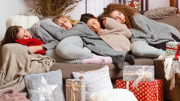Vier junge teenager-mädchen schliefen auf der couch ein, nachdem sie weihnachtsgeschenke eingepackt hatten