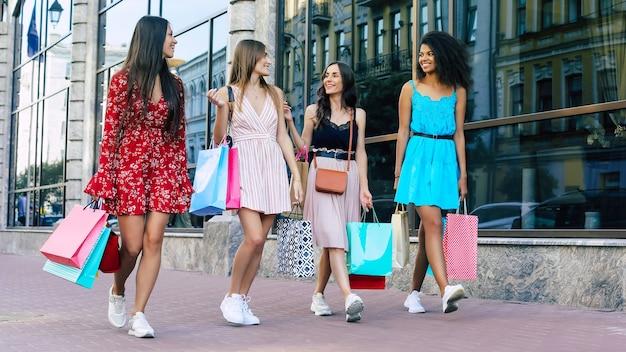 Vier junge und schöne frauen in sommerkleidern laufen gemeinsam durch die straßen der stadt, tragen einkaufstüten und unterhalten sich lebhaft