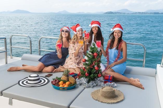 Vier kaukasische freundinnen feiern eine weihnachtsfeier auf einer yacht