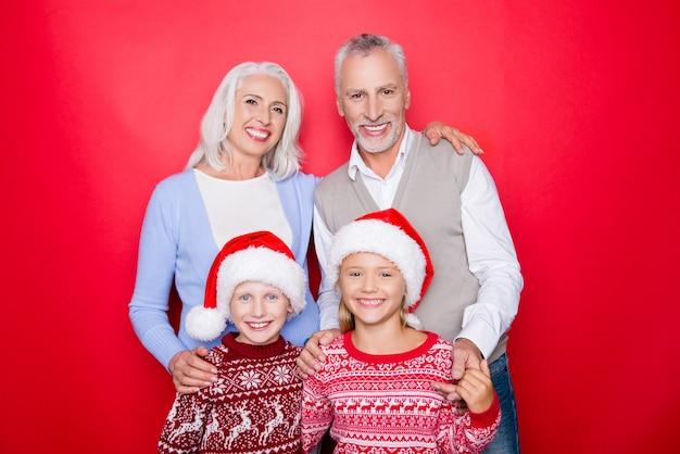 Vier kaukasische verwandte verbinden sich isoliert auf dem roten raum, verheiratetes älteres paar von opa und oma, grauweißes haar, aufgeregte geschwister, in gestrickten niedlichen traditionellen weihnachtskostümen, zusammengehörigkeit
