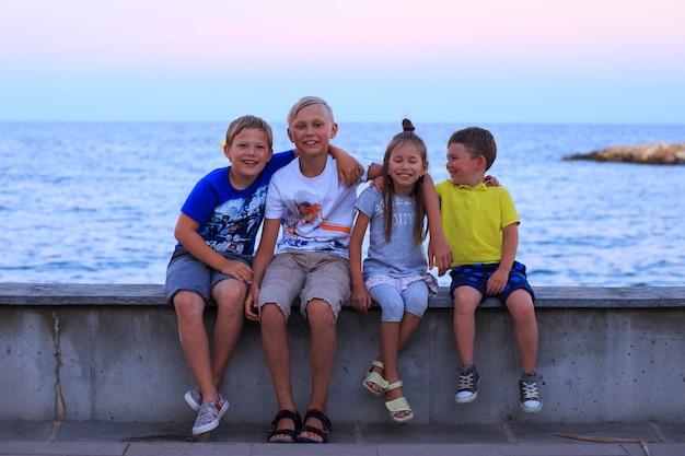 Vier kinder am strand berufung junge familie im urlaub haben viel spaß