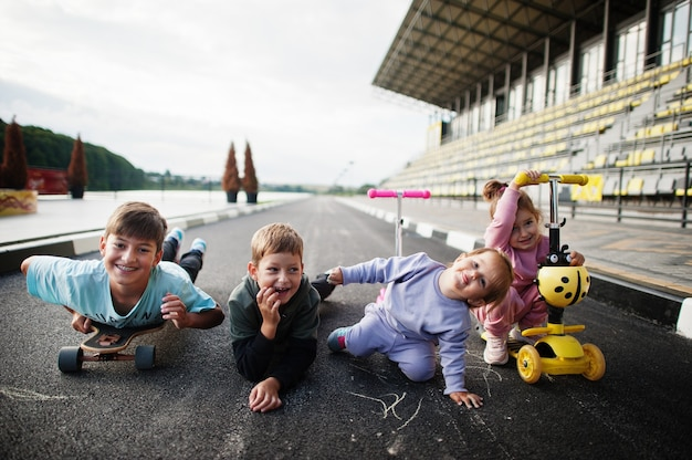 Vier kinder in asphalt spielen und spaß haben. sportfamilie verbringen ihre freizeit im freien mit rollern und schlittschuhen.
