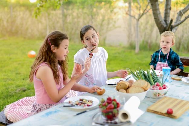 Vier kinder sitzen am tisch in der natur und essen.