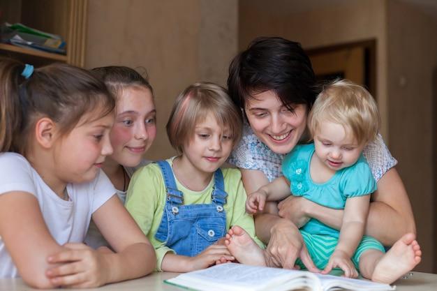 Vier kinder unterschiedlichen alters von 2 bis 14 jahren am tisch mit buch und mutter