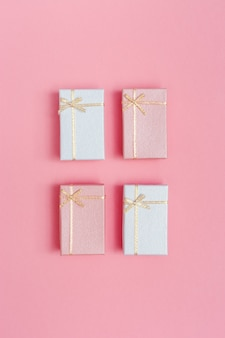 Vier kleine rosa und weiße geschenkboxen. minimaler stil des konzepts oder der grußkarte. romantische draufsicht