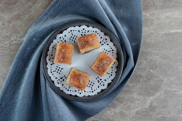 Vier köstliche baklava auf dunklem teller