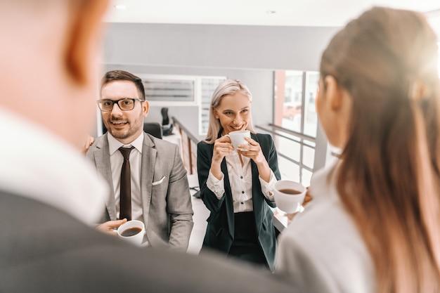 Vier kollegen in abendgarderobe unterhalten sich und trinken in der pause kaffee. unternehmensgeschäftskonzept. sie unterstützen entweder die vision oder die teilung.