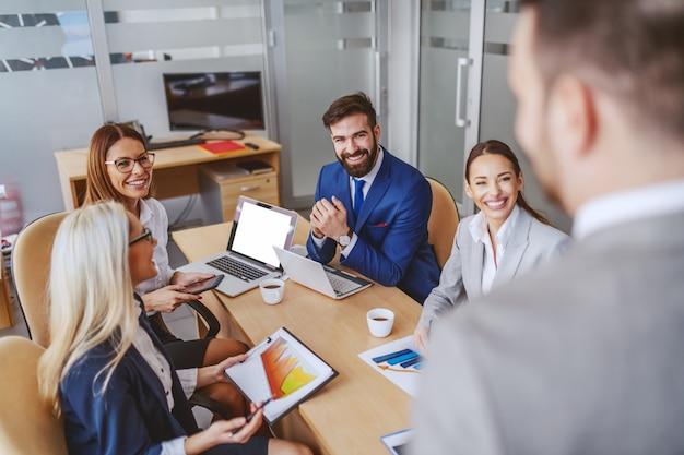 Vier kollegen sitzen im sitzungssaal und hören ihrem chef zu