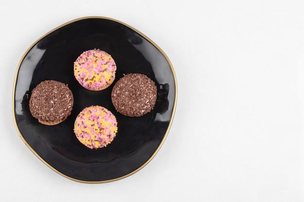 Vier-kreis-keks-marshmallows mit bunten streuseln auf schwarzem teller