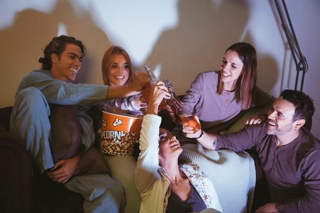 Vier lachende freunde, die einen film ansehen