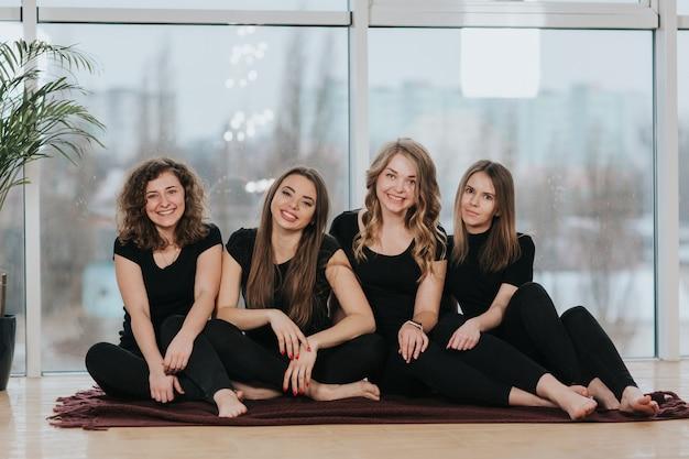 Vier lächelnde mädchen posieren an der kamera, die am fenster sitzt