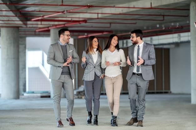 Vier lächelnde positive architekten sprechen und besuchen gebäude im bauprozess